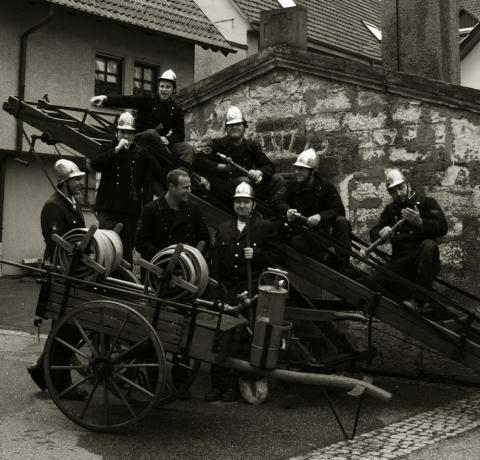 Feuerwehrleute auf Spritzenwagen
